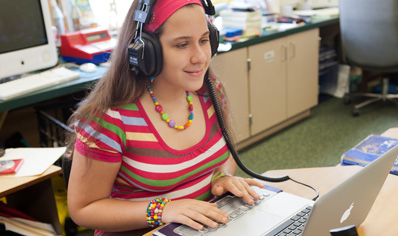Student with headphones using an MacBook Pro.