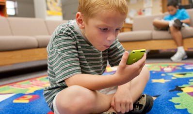 Student sitting on rug looking at iPod touch.