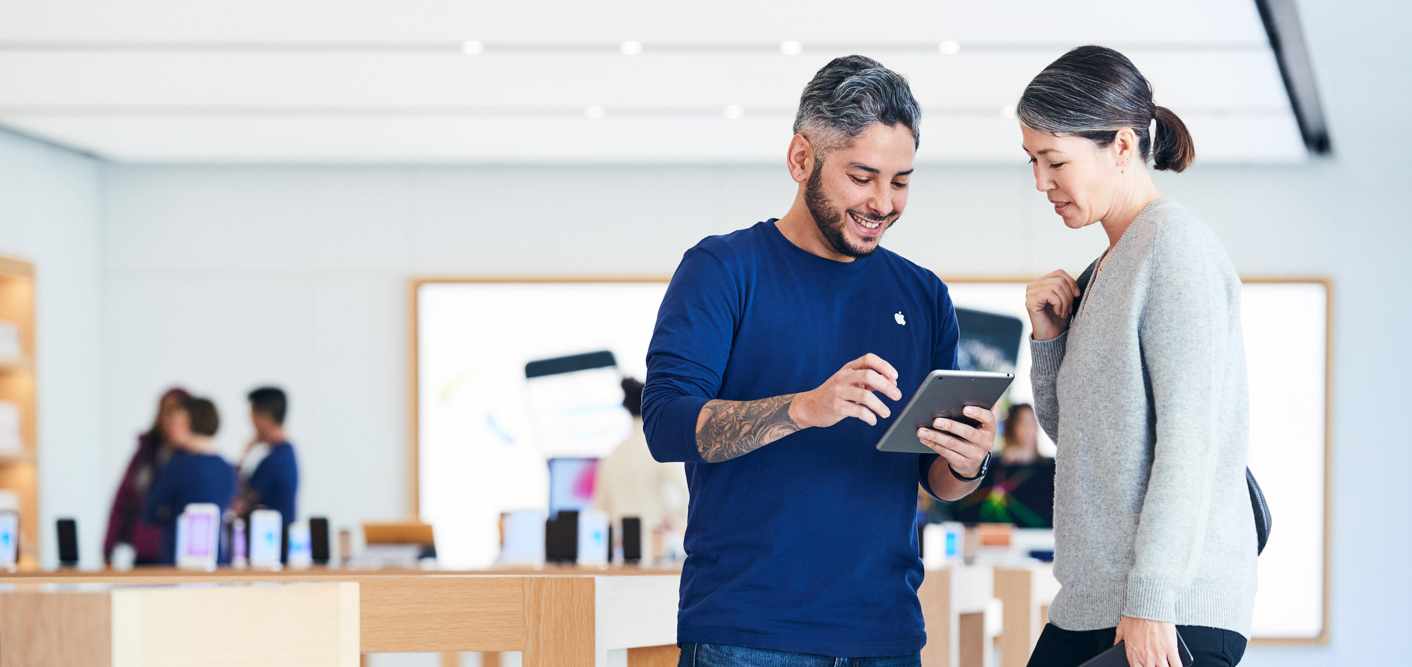 An Apple Store employee shows a customer the features of iPad