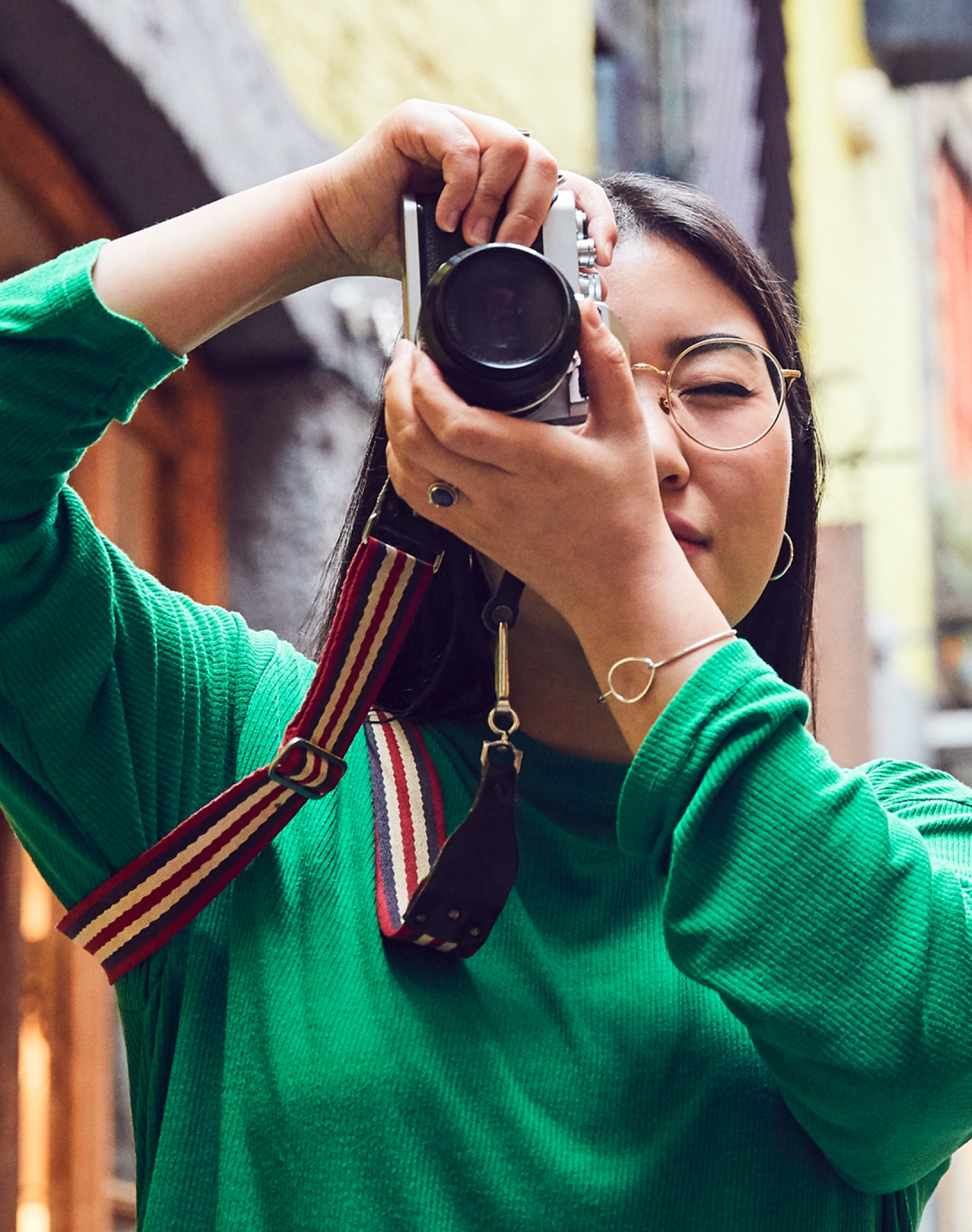A female Apple Store employee takes photos with a traditional 35mm camera on a city street.