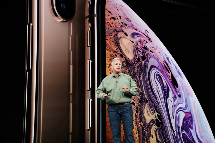 Phil Schiller in front of iPhone Xs screen on stage.