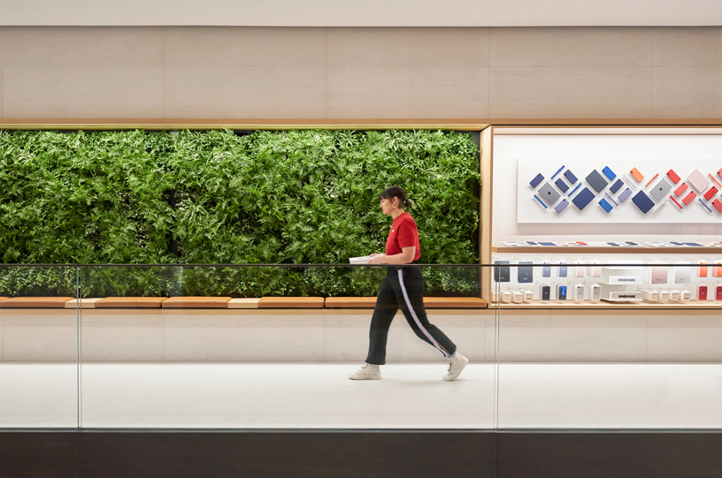An Apple team member in front of the green wall at Apple Champs-Élysées.