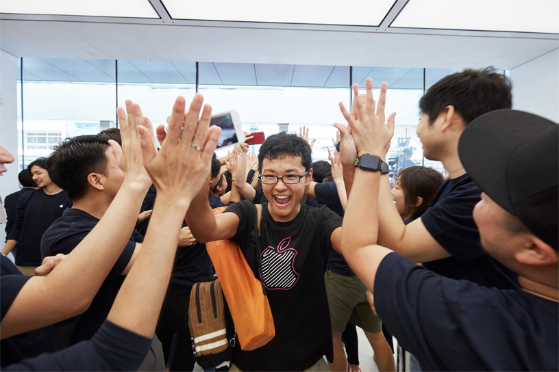 Customer getting high fives from Apple Kyoto team members.