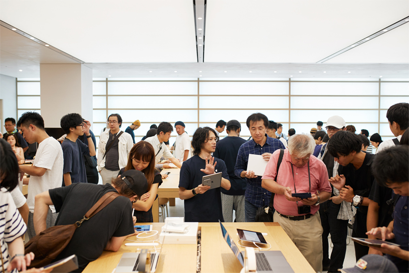 Crowd of customers mingling with employees at Apple Kyoto.