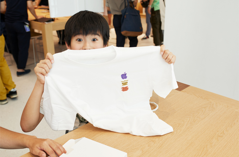 Customer at Apple Kyoto holding up a commemorative t-shirt.