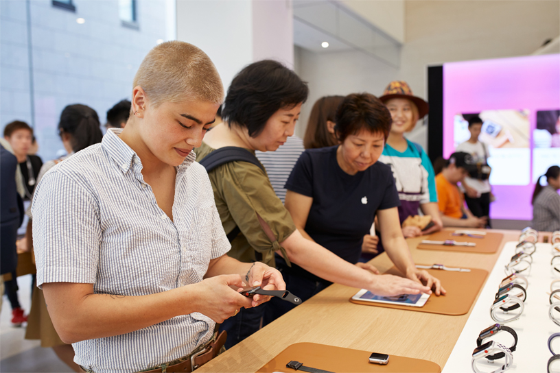 People looking at Apple Watches at a table at Apple Kyoto.