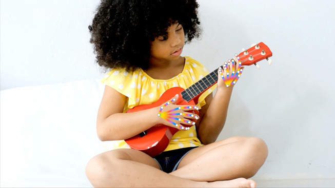 A child playing a Ukulele to demo hand pose detection.