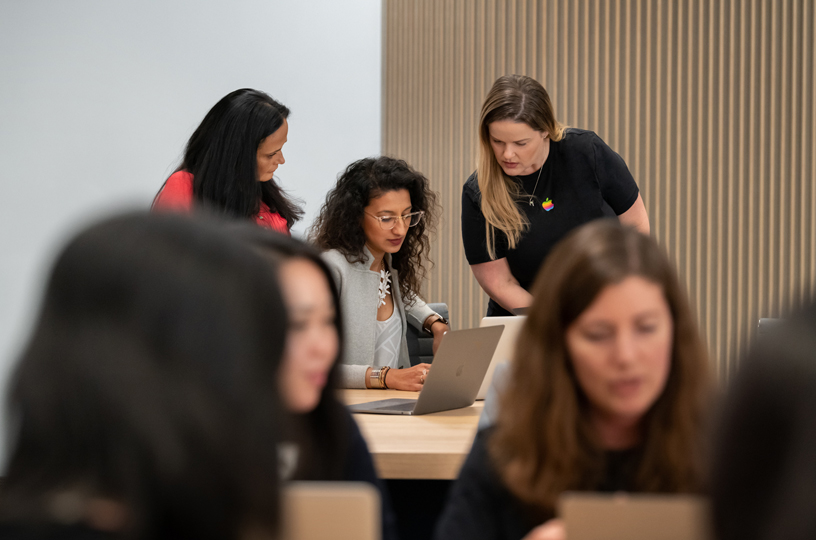 Women working behind a MacBook with two instructors.