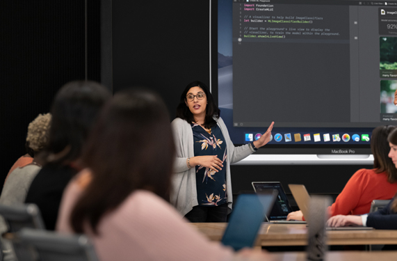 An instructor displaying coding on a MacBook Pro in front of a class of participants.