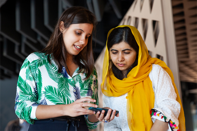 Malala Yousafzai looks at an iPhone with a woman at the Apple Developer Academy in Rio.