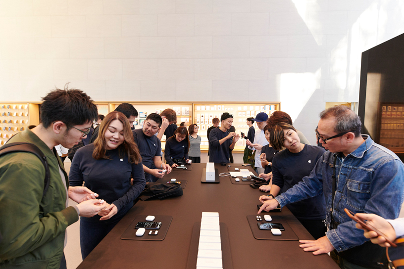 Apple team members assist customers around a table at Apple Omotesando in Tokyo.