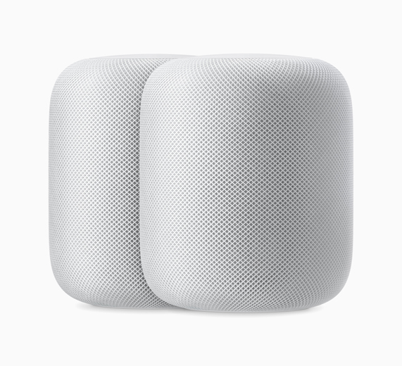 A photo of two white HomePods sitting side by side.