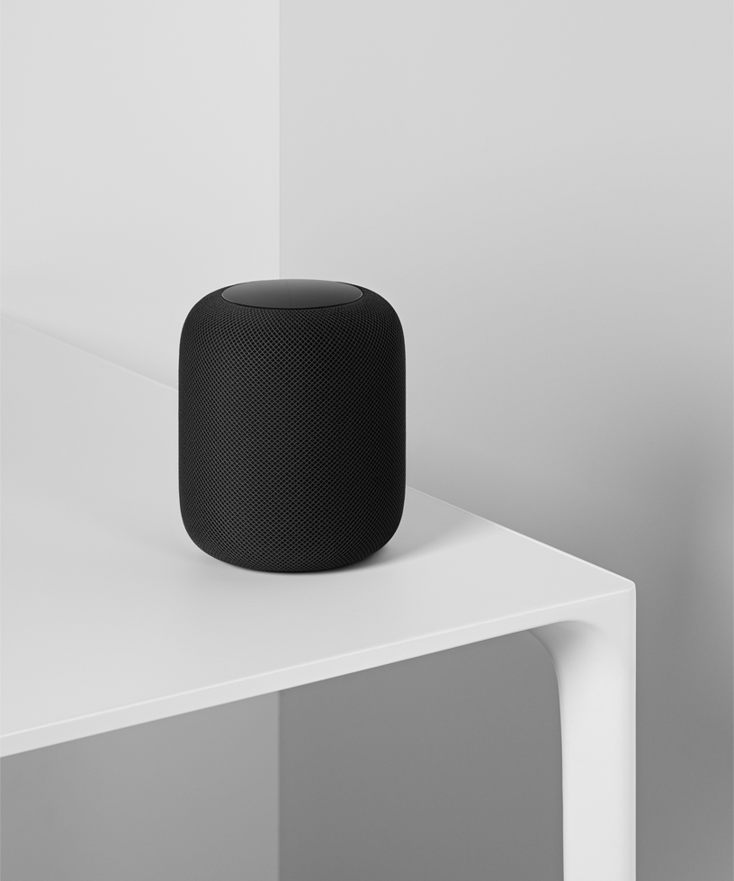 A photo of the space gray HomePod sitting on a white table.