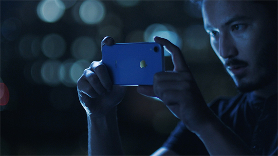 Man taking picture with a blue iPhone XR at night.