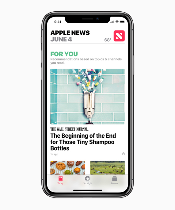 iPhone X showing Apple News app with For You recommendations.