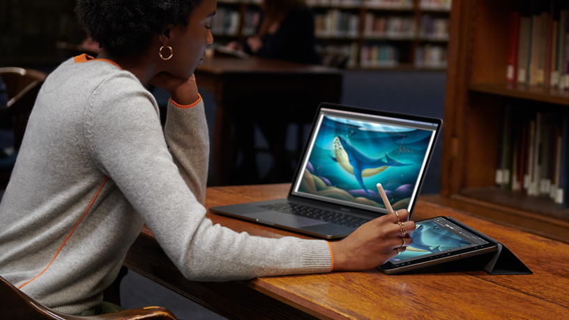 Woman using MacBook and iPad with Sidecar.