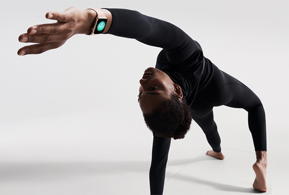A woman performing a yoga pose on a mat, wearing Apple Watch Series 4 in gold.